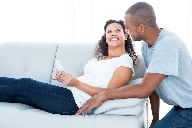 Cheerful young couple looking at each other relaxing at home
