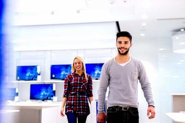 Веселая молодая пара ищет новые электронные устройства в магазине