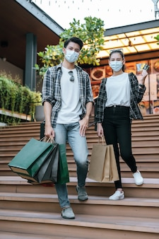Cheerful young couple in mask holding multiple paper shopping bag