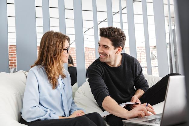 ラップトップを使用して、オフィスで一緒に働いている同僚の陽気な若いカップル、共同作業チームワークの概念