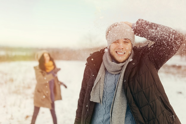 Cheerful young couple playing snowballs