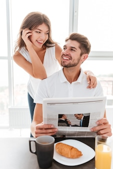 Cheerful young couple reading newspaper and having breakfast at home