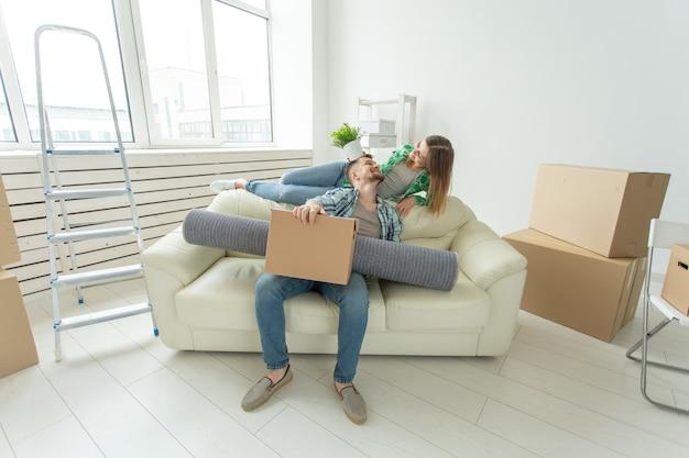 Веселая молодая пара радуется переезду в новый дом, раскладывая свои вещи в гостиной