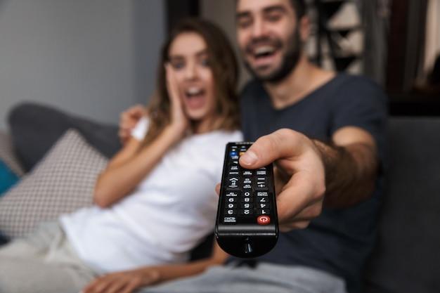 テレビを見ながら、自宅のソファでリラックスした陽気な若いカップル