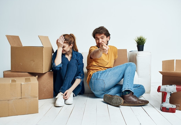 Cheerful young couple in the room on the couch with boxes