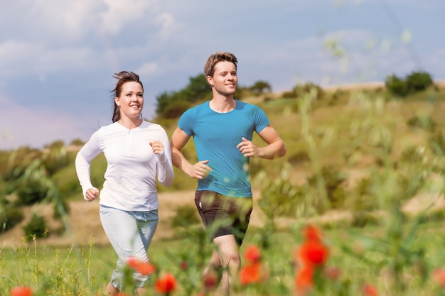 Cheerful young couple running between flowers in a sunny meadow