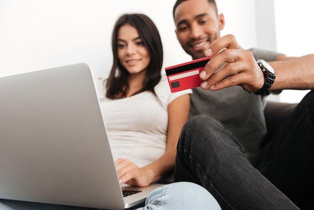 Веселая молодая пара, делающая покупки в интернете, сидя на диване в помещении. женщина смотрит на ноутбук. человек, держащий кредитную карту.