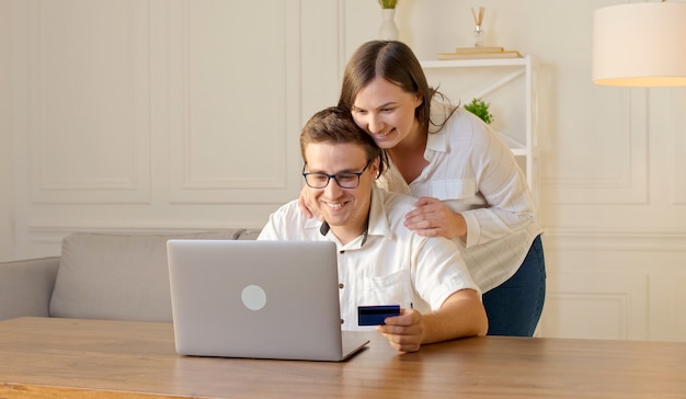 Cheerful young couple shopping online while sitting home with credit card and laptop computer
