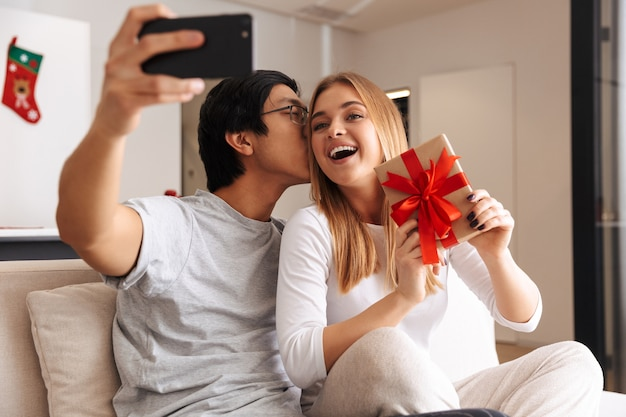 Cheerful young couple, sitting on a couch at home, taking a selfie, showing present box