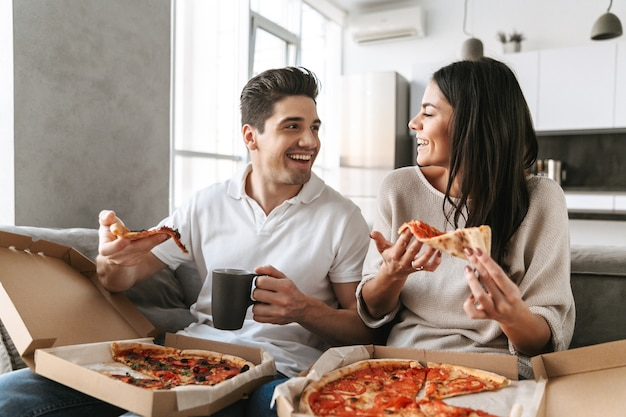 自宅のソファに座って、ピザを食べて陽気な若いカップル