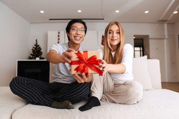쾌활 한 젊은 부부, 집에서 소파에 앉아 선물 상자를 보여주는