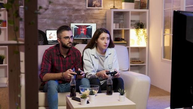 쾌활한 젊은 부부는 소파에 앉아서 텔레비전에서 비디오 게임을 하고 있습니다. 행복한 관계