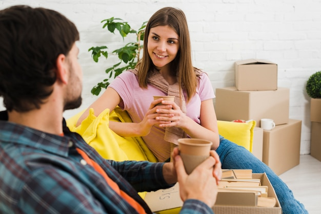 Cheerful young couple sitting on sofa drinking coffee while cardboard boxes laying all around them