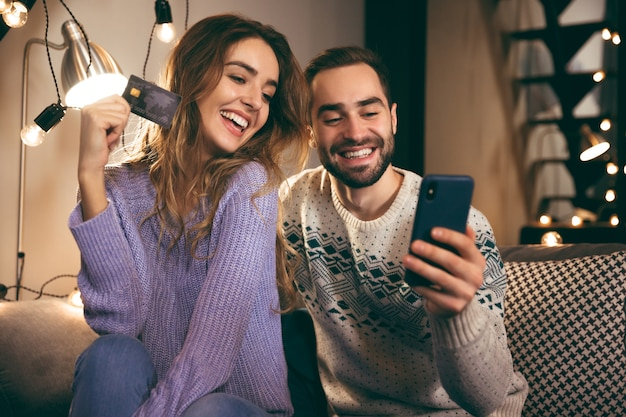 Cheerful young couple sitting together on a couch at home, holding mobile phone, showing plastic credit card