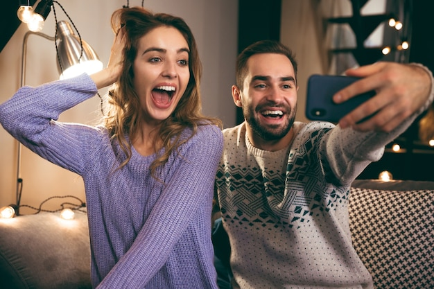Cheerful young couple sitting together on a couch at home, taking a selfie