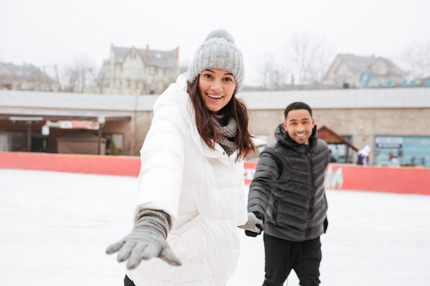 Cheerful young couple skating at outdoor rink