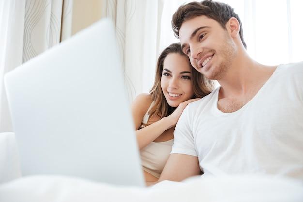 Веселая молодая пара улыбается и использует ноутбук в постели