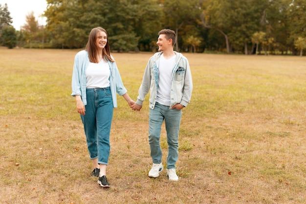 笑顔で屋外を歩く陽気な若いカップル