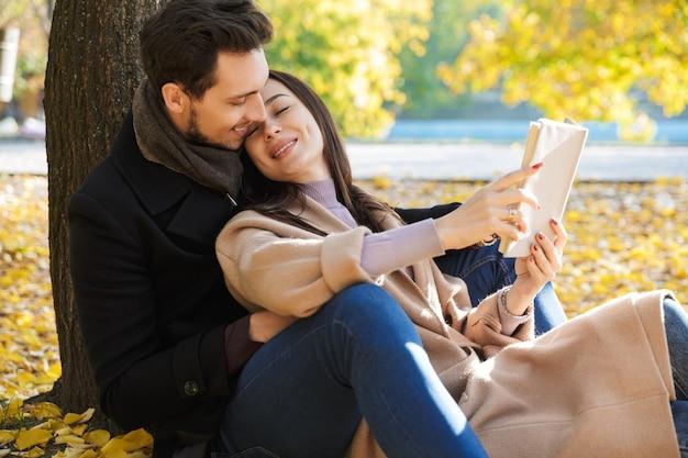 Веселая молодая пара весело проводит время в парке осенью, сидя, читая книгу