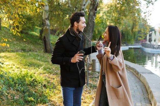 秋の公園で楽しい時間を過ごしたり、手をつないで歩いたり、イヤホンで音楽を聴いたりする陽気な若いカップル