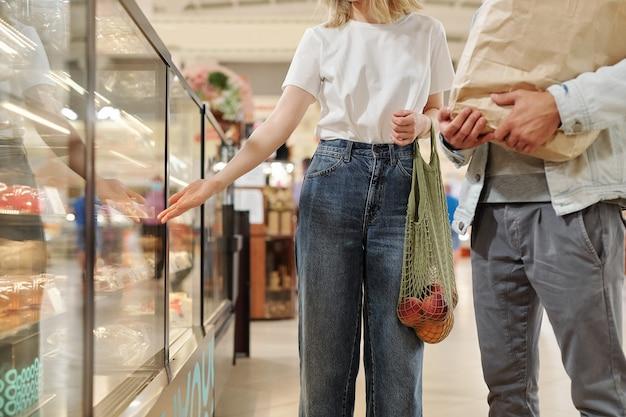 ファーマーズマーケットに立ち、買い物を楽しみながらおしゃべりする元気な若いカップル