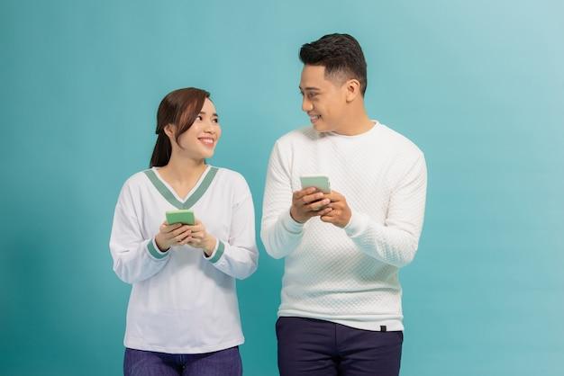 青の上に孤立して立って、カジュアルな服装でスマートフォンを保持している陽気な若いカップル