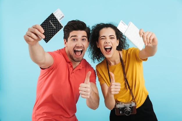 Веселая молодая пара стоя изолированно, показывая паспорта с авиабилетами
