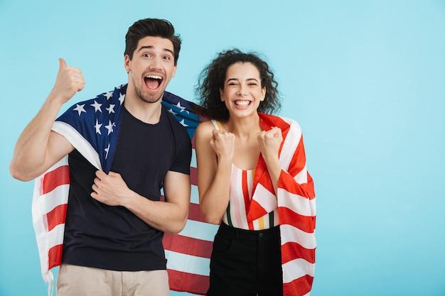 孤立して立って、アメリカの国旗を身に着けている陽気な若いカップル