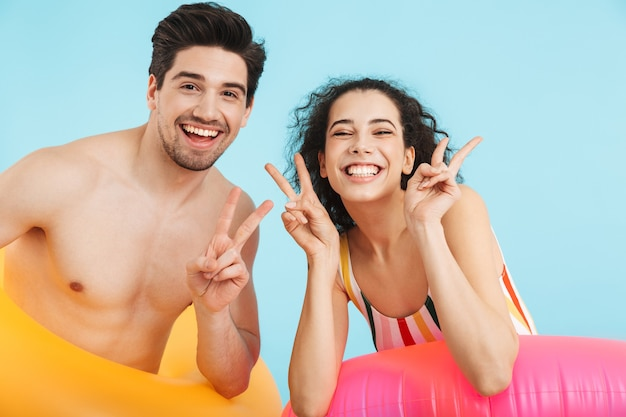インフレータブルリングを身に着けて、孤立して立っている陽気な若いカップル