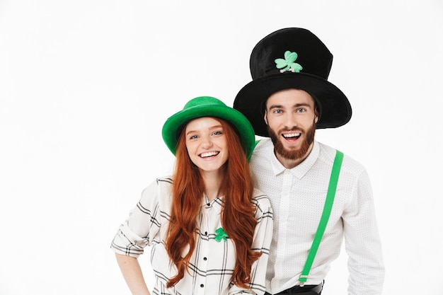Cheerful young couple standing isolated over white wall, celebrating stpatrick 's day