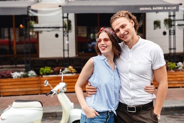 Веселая молодая пара, стоя вместе с мотоциклом на городской улице