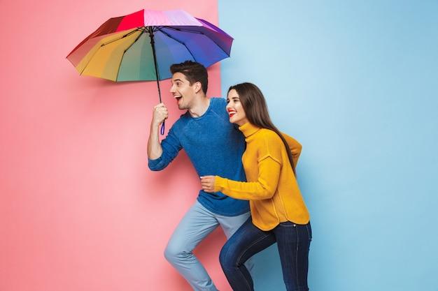 傘をさして立っている陽気な若いカップル