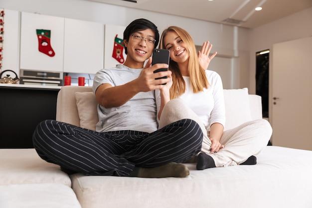 Веселая молодая пара, делающая селфи, сидя на диване у себя дома