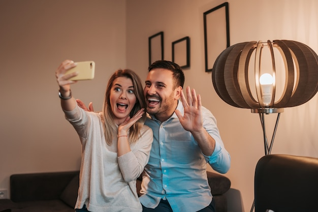 Cheerful young couple taking selfie indoors.