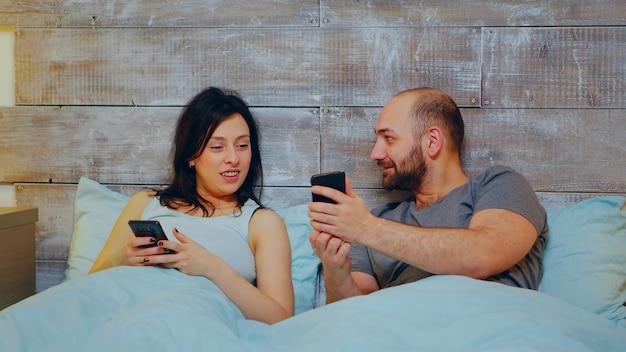 Веселая молодая пара с помощью смартфона в пижаме в постели ночью перед сном.