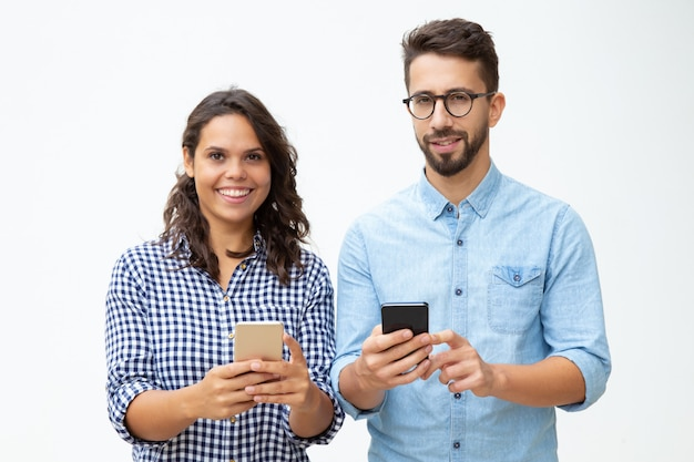 Cheerful young couple using smartphones