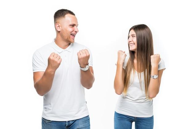 陽気な若いカップルの勝利の成功の概念が白で隔離