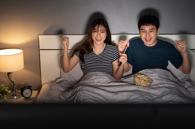 Веселая молодая пара смотрит спортивный телевизор с поднятой рукой на кровати ночью