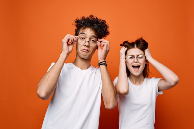 Cheerful young couple in white t-shirts emotions communication orange background. high quality photo