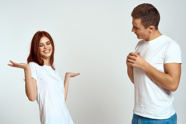 Cheerful young couple in white tshirts communication emotions lifestyle studio