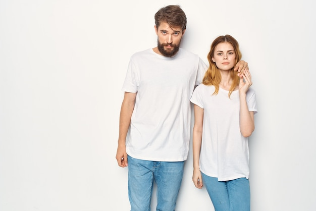 Cheerful young couple in white tshirts embrace friendship lifestyle