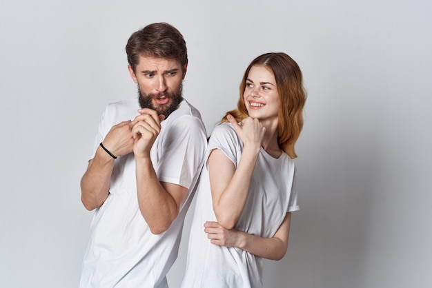 Cheerful young couple in white tshirts posing fashion light background