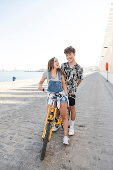 Cheerful young couple with bicycle having fun