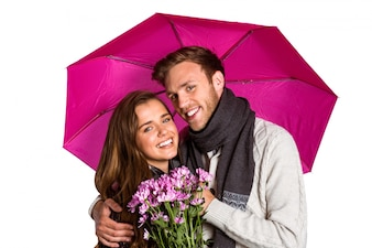 Cheerful young couple with flowers and umbrella