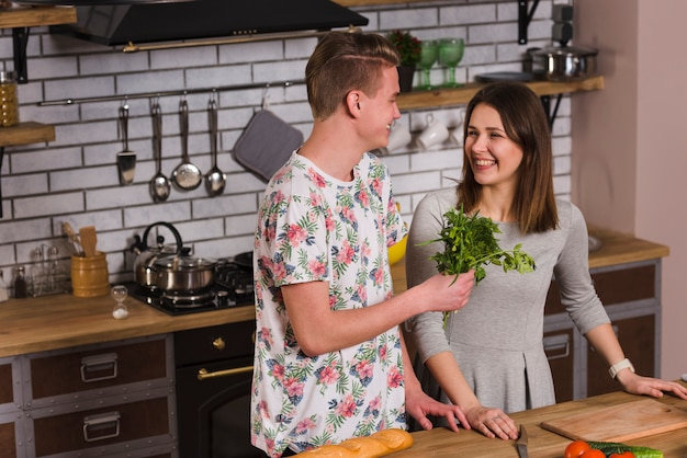 Cheerful young couple with herbs