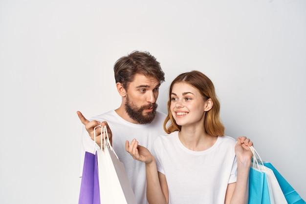 エンターテインメントの友情をショッピング手にパッケージを持つ陽気な若いカップル