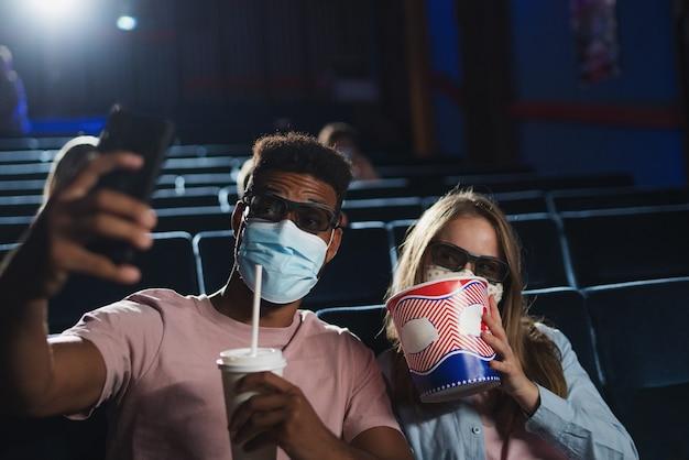 映画館で自分撮りをしているポップコーンと3dメガネ、コロナウイルスの概念を持つ陽気な若いカップル。
