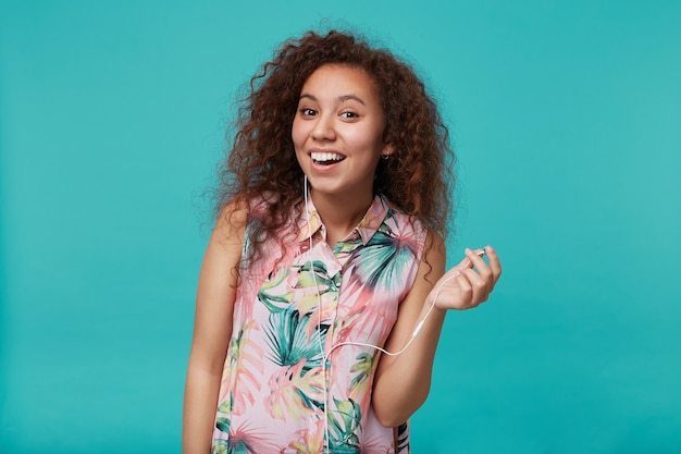 夏の花のシャツで青に立っている間、イヤホンを取り出して幸せそうに笑っている陽気な若い巻き毛のブルネットの女性