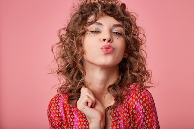Cheerful young curly brunette female with festive hairstyle and multicolored dots on her face standing, folding lips in air kiss and looking joyfully