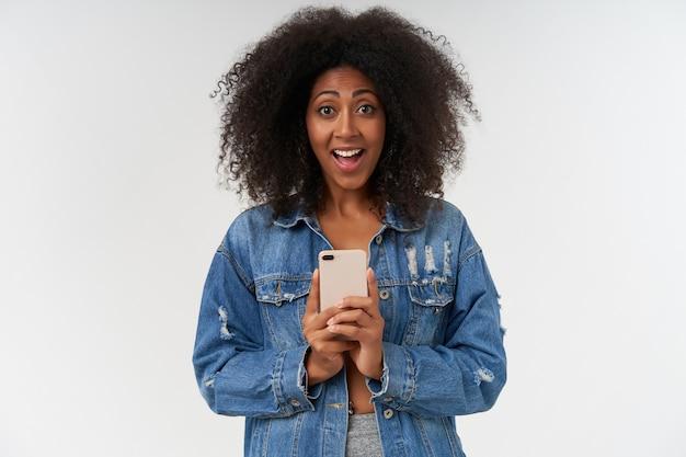 携帯電話を手に持って写真を撮る陽気な若い巻き毛の暗い肌の女性は、カジュアルな服を着て白い壁にポーズをとっている間、広く笑っています。